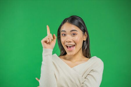 Beautiful cheerful asian businesswoman with idea showing pointing finger up on green background
