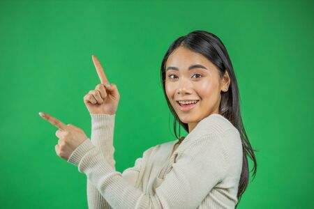 Portrait of beautiful 20s Asian woman wearing adorable dress expressing happiness pointing fingers sideways at copyspace isolated on green background 版權商用圖片