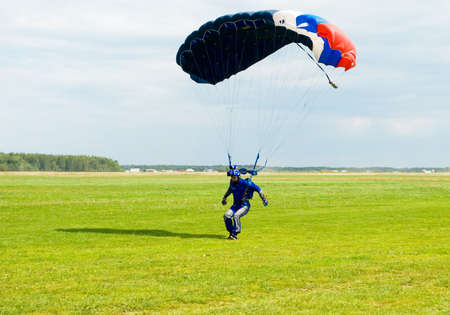 Landing of the videotape operator after parachute jump Stock Photo