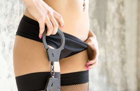 The girl dressed in underwear holds handcuffs photo