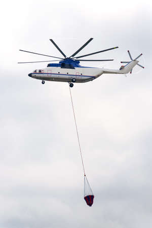 elimination: Fire helicopter flies in sky and has a water tank for fire fighting Stock Photo