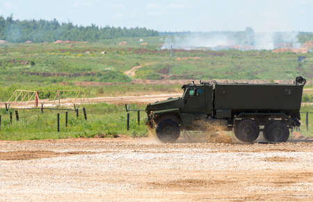 armored truck: The military vehicle goes on the dusty road Stock Photo