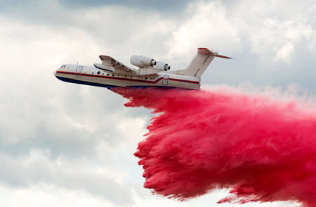 Flying aerial firefighting pour water over the fire Stock Photo