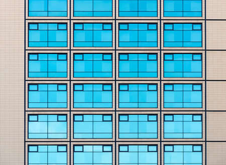 Modern minimalistic architecture with a lot of square glass windows and colors on the building. The rhythm of the windows. Geometric pattern.