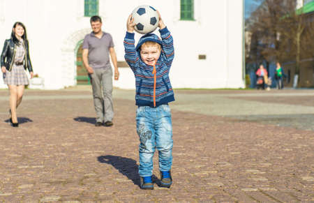 Cute little boy is walking in a park with his parents and carrying soccer ball 写真素材