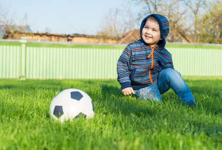 Young boy laying on an green grass. Nearby the ball lies Archivio Fotografico