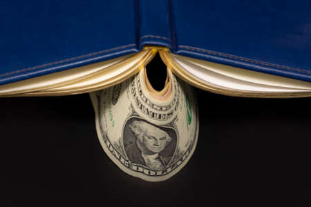 dollars banknotes and blue diary with a clip lie on black background. Finance