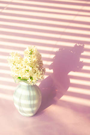 Fresh branch of a white lilac with a small vase. Summer bouquet.