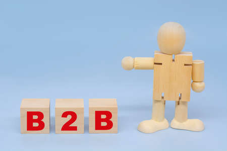 A wooden figure of a man points to an inscription B2B on wooden cubes. Business and corporate concepts