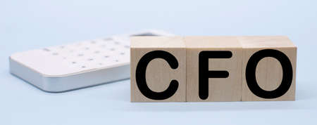 text CFO - Chief Financial Officer of wooden blocks CFO and white calculator. Chief Financial Officer acronym on wooden cubes on blue backround. Business concept.