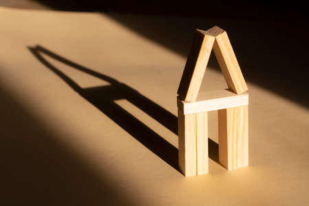 the house is made of wooden blocks and shade. Real estate market or agent concept.