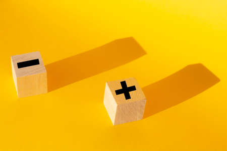 plus and minus on a yellow background. Business concept. Risk Stock fotó