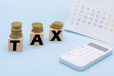 word tax on wooden cubes, coins, calculator and notepad. Business and tax concept. Pay tax