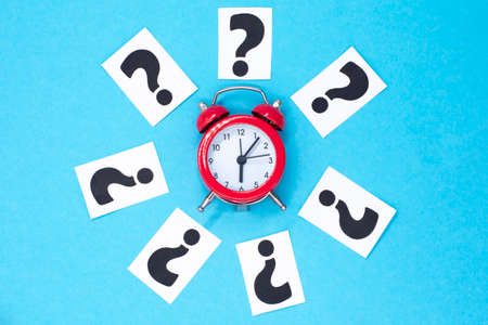 a question mark on a white sheet and a red alarm clock. FAQ frequency asked questions, Answer and Brainstorming Concepts