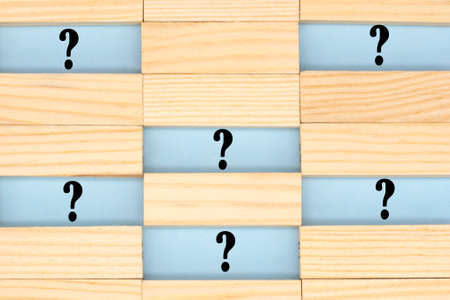 Question mark among the wooden blocks. Answer search concept.