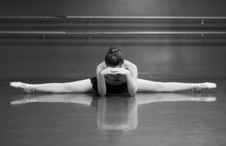 Black   White photo of a ballerina stretching her middle splits, in the studio with barre background  photo