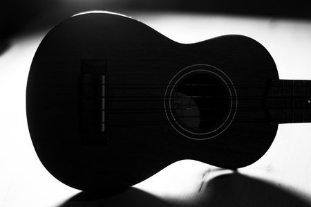 studio b: B W shot of a ukulele laying on its side  Backlit with dramatic contrast and shadows  Stock Photo