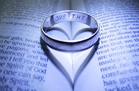 Gegraveerd trouwring maken hart schaduw op open Bijbel Stockfoto