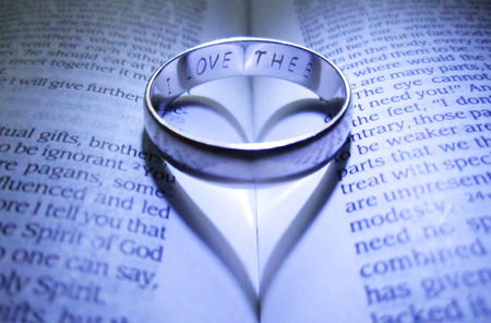 Engraved wedding band making heart shadow on open Bible