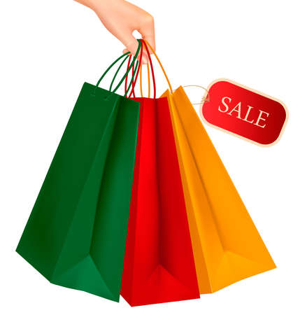 Female hand holding colorful shopping bags with sale tag. Concept of discount. Vector illustration. Vector