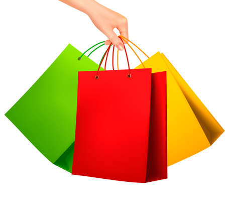 gift bags: Female hand holding colorful shopping bags. Vector illustration.