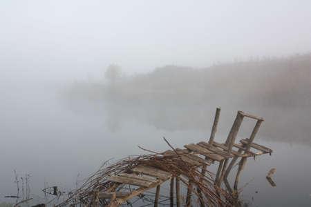 decrepit: Old, decrepit, rickety bridge on the river a misty morning