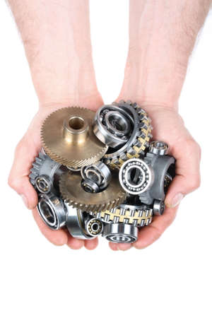 Hands hold a heap of bearings and a gear wheel on a white background photo