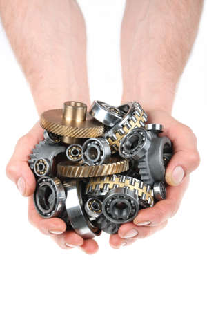 grip: Hands hold a heap of bearings and a gears wheel on a white background