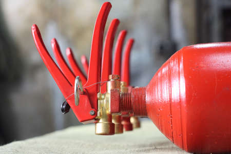 fire extinguishers: Four fire extinguishers are in a row on the table Stock Photo