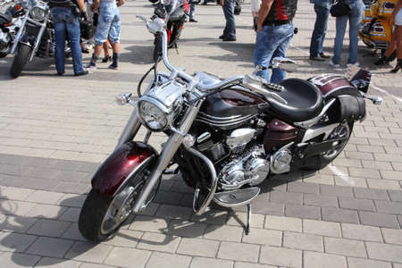 Motorcycle dark - cherry colored, stands on the sidewalk tile photo