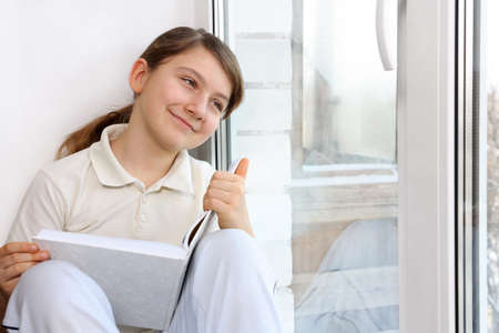 Girl at the window with a book in their hands photo