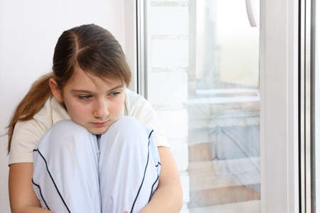 Girl sitting on the windowsill, looking out the window with a sad expression on her face photo