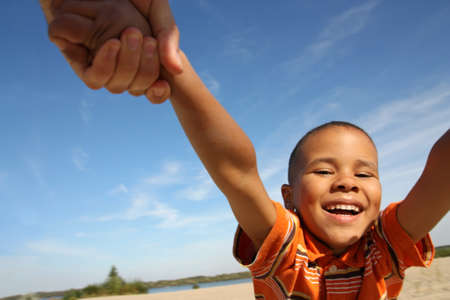circling: Happy boy. Little black boy playing on the beach, circling hand in hand.