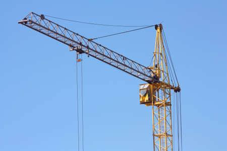 Yellow construction crane against a blue sky photo