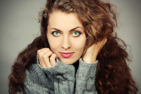 Beautiful young woman in a gray sweater with a gray background photo