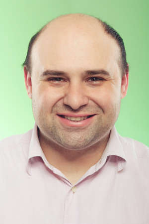 bald men: Portrait of a real smiling  man in the studio on a green background Stock Photo