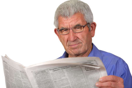 Senior with glasses reading a newspaper on a white background photo