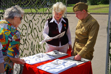 leaflets: The celebration of May 1 - International Workers Day. Young people in the form of a soldier handing out leaflets. Dnepropetrovsk. Ukraine