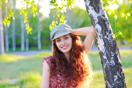 european white birch: Redhead beautiful girl in a cap looks into the camera on outdoors Stock Photo
