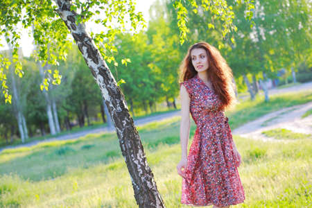 cute lady: Beautiful red-haired girl in dress posing in nature