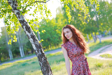 european white birch: Beautiful red-haired girl in dress posing in nature