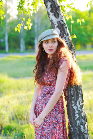 european white birch: Redhead beautiful girl in a cap standing near tree