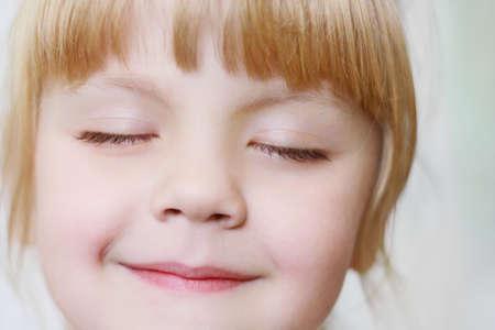Gezicht van een klein meisje met gesloten ogen close-up
