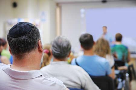 会議室における実習のスピーカーに耳を傾ける人