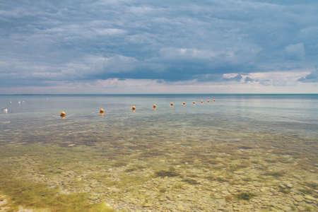 Rust zeegezicht, stenen op de bodem van de kalme zee tegen de bewolkte hemel Stockfoto