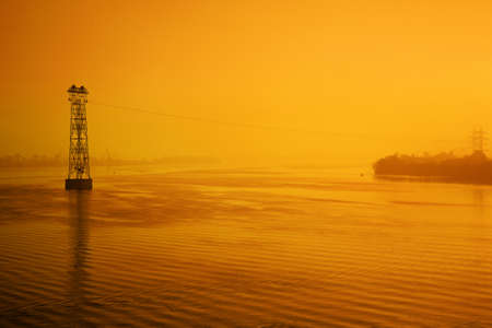Industrial landscape, high voltage line across the river at sunset