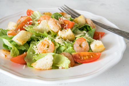 Caesar salad with shrimps, cherry tomato, croutons, salad leaf and parmesan cheese.