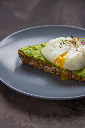 Sandwich with avocado and poached egg. Healthy breakfast.
