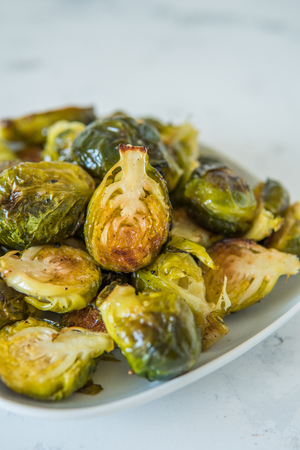Cooked Brussels sprouts in a white plate.