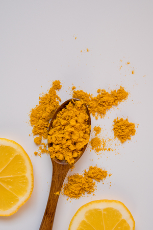 Turmeric in a wooden spoon and two lemon slices top view.
